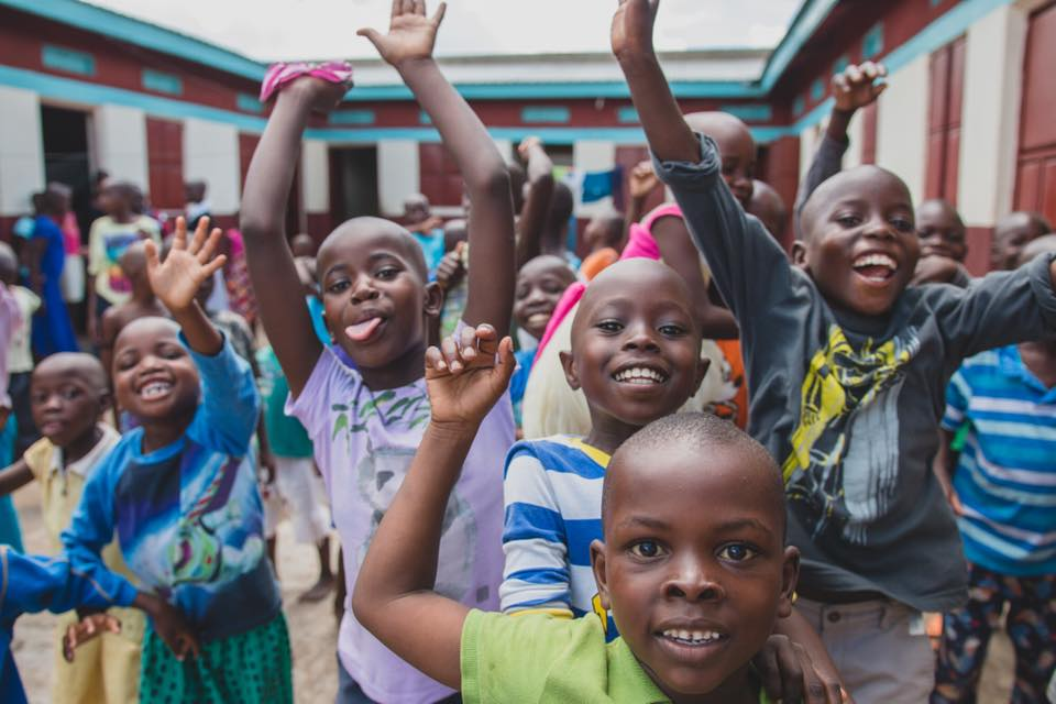African children rejoice with lifted hands and grins.
