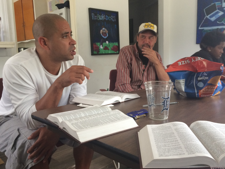 A few people gather for Bible study around a table.