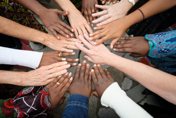 Hands of differing skin tones meet in a circle.