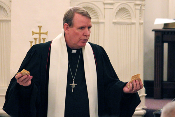 Rev. Dr. Gregg Mast holding communion bread