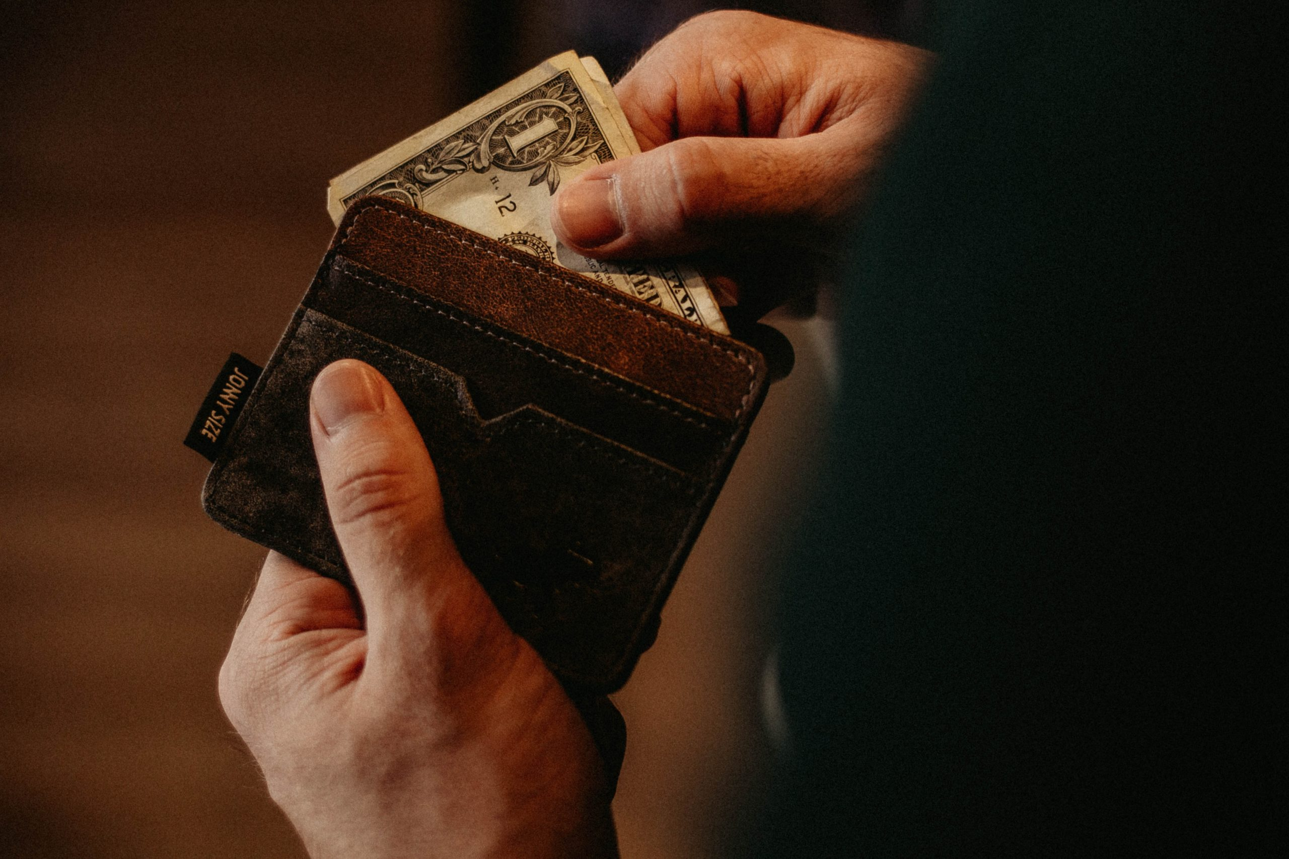 Hands place dollar bills into a brown leather wallet.