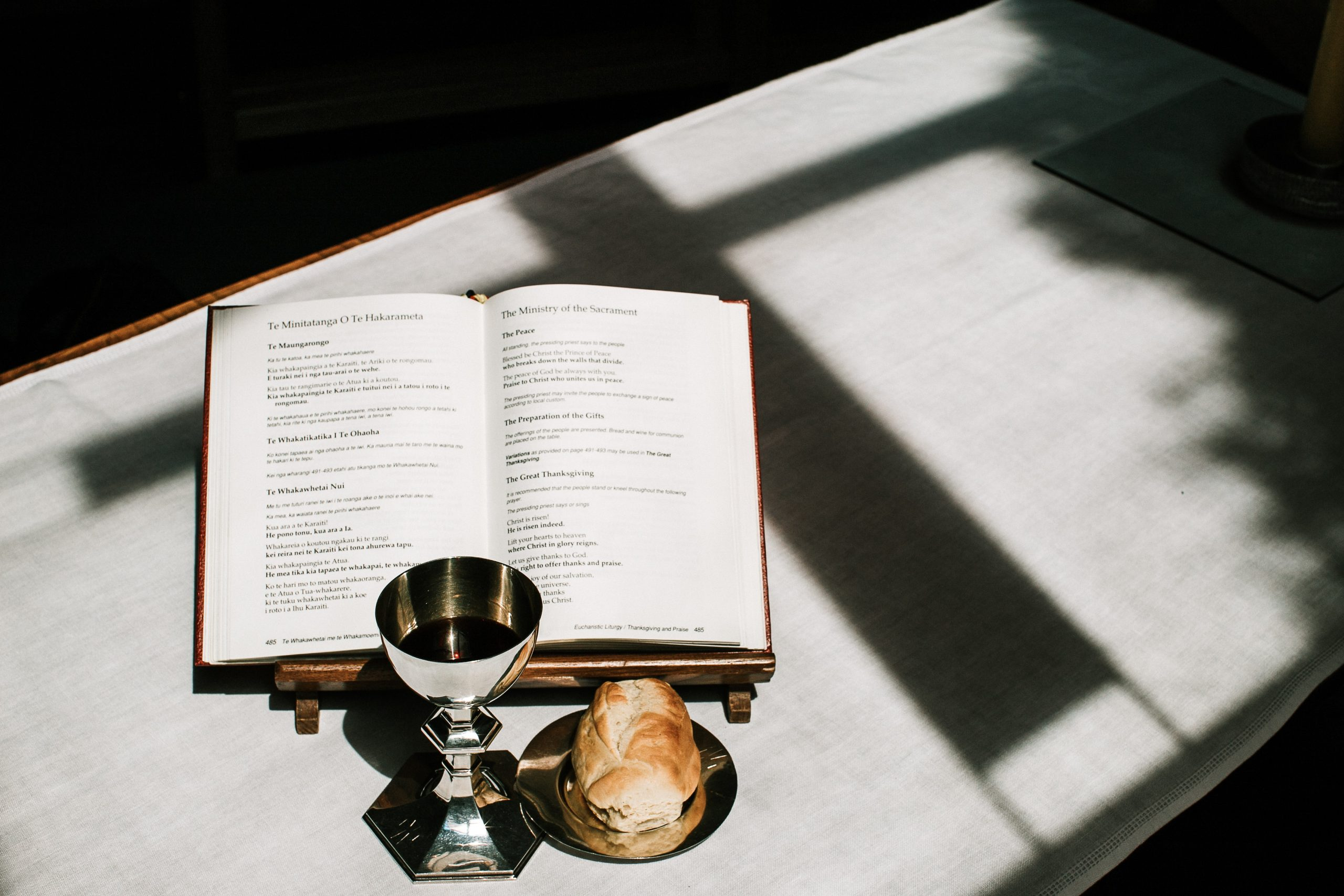 A loaf of bread and silver goblet sit next to a book opened to a communion liturgy. A shadow of the cross darkens the table upon which the communion elements are set.