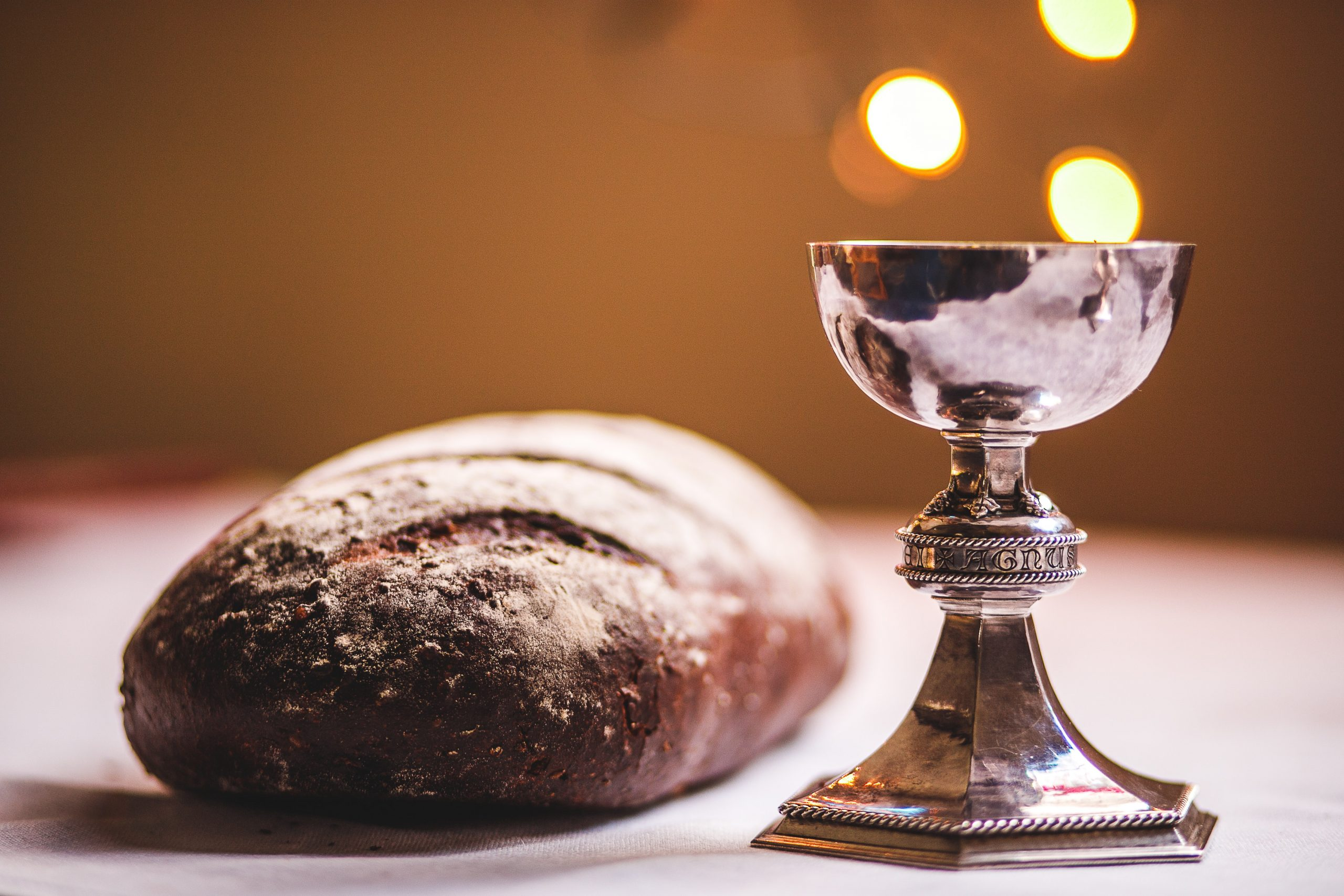 A loaf of bread and a silver goblet are prepared for the sacrament of communion.