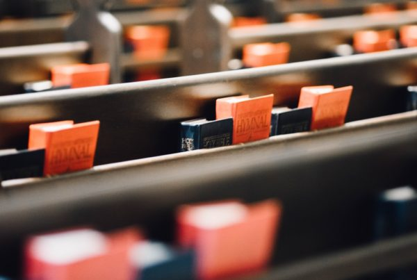 Black Bibles and red hymnals line the backs of church pews.