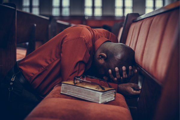 A man kneeling with his head bowed on a pew in prayer; a Bible is on the pew next to him